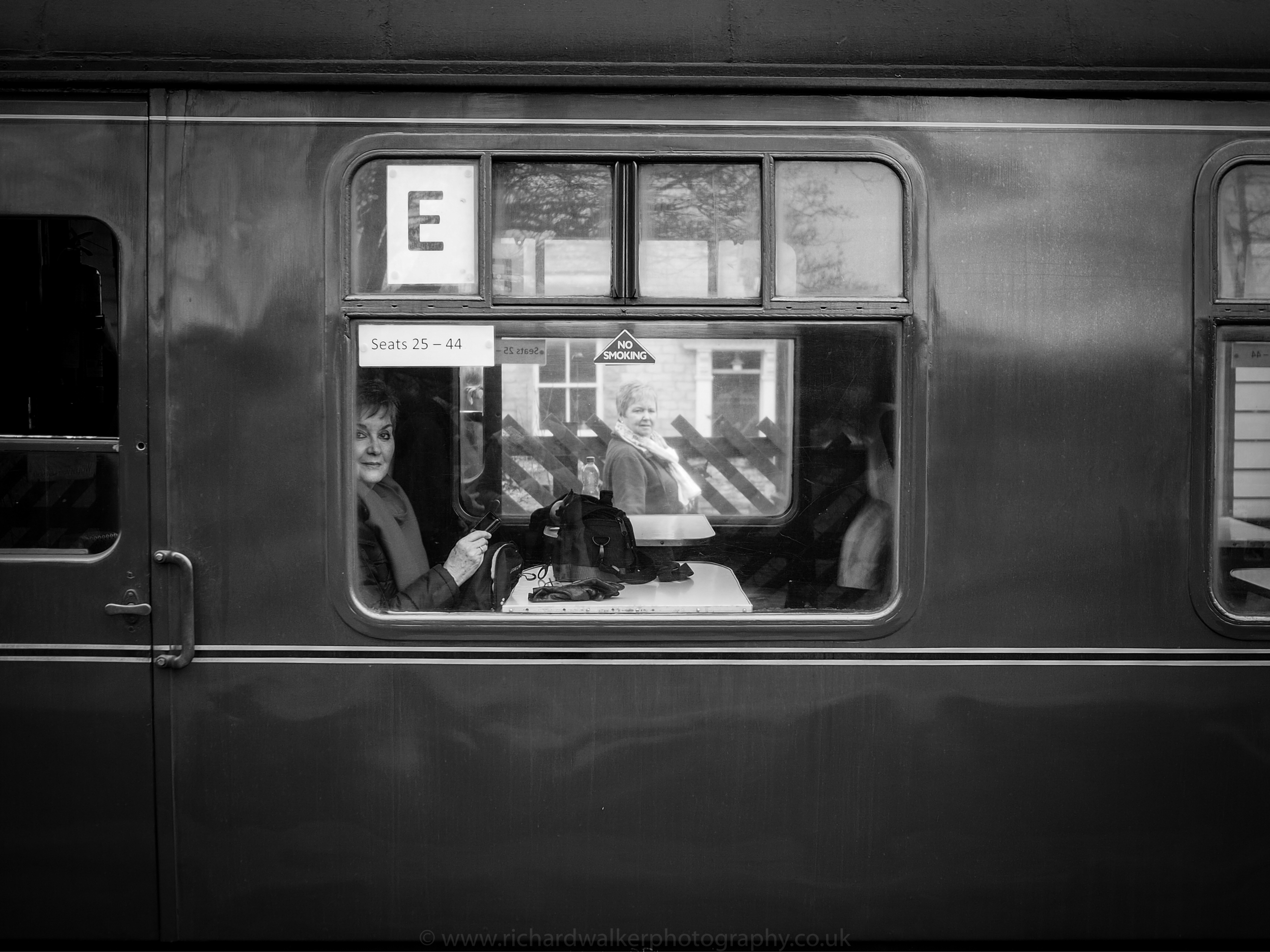 A female passenger sitting on a carriage of the Flying Scotsman looking out of the window