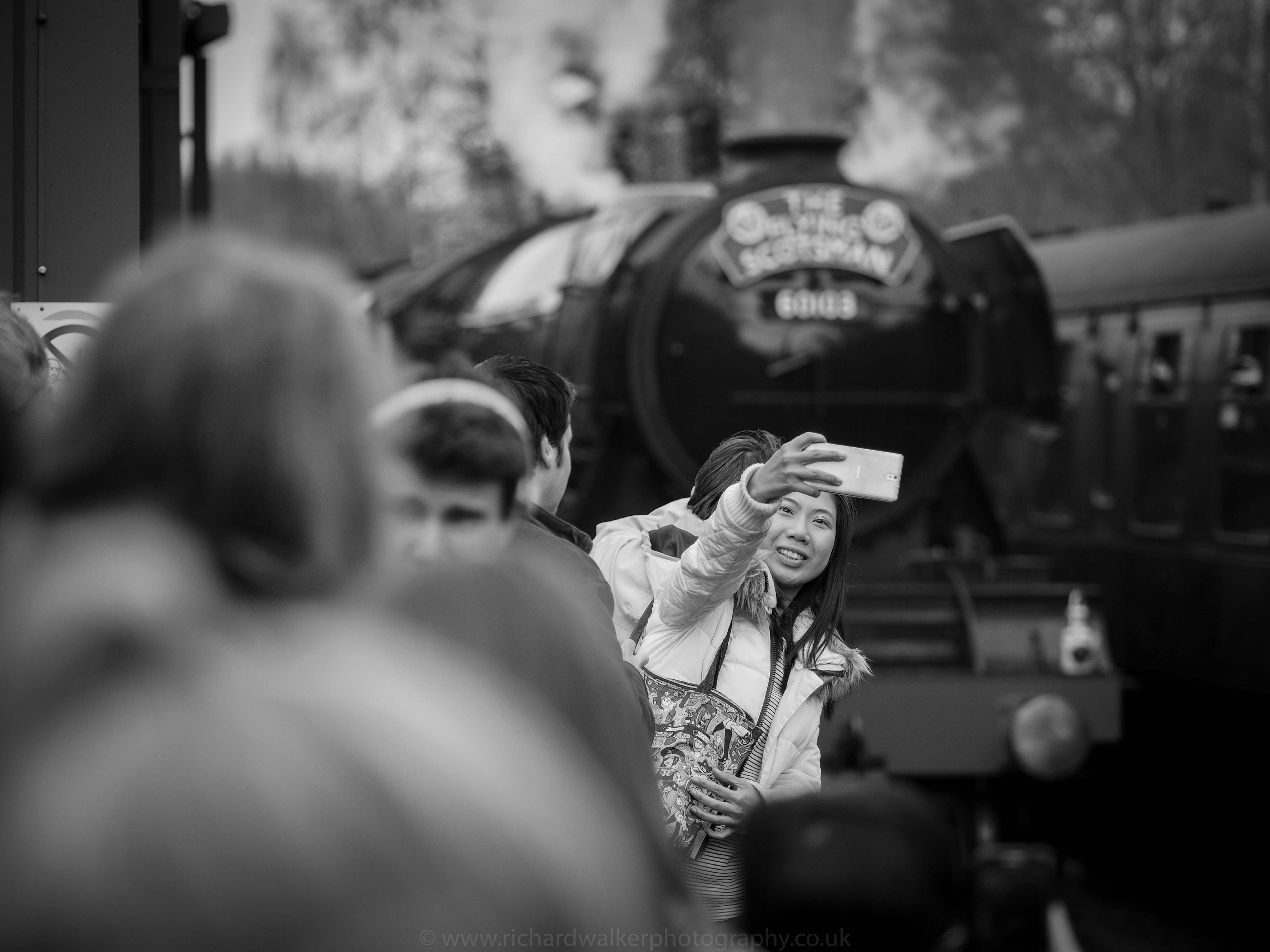 A tourist taking a selfie with the Flying Scotsman behind at Pickering Station