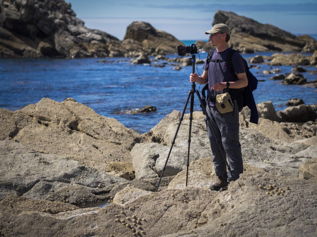 Award winning landscape photographer Richard Walker standing on rocks at the coast