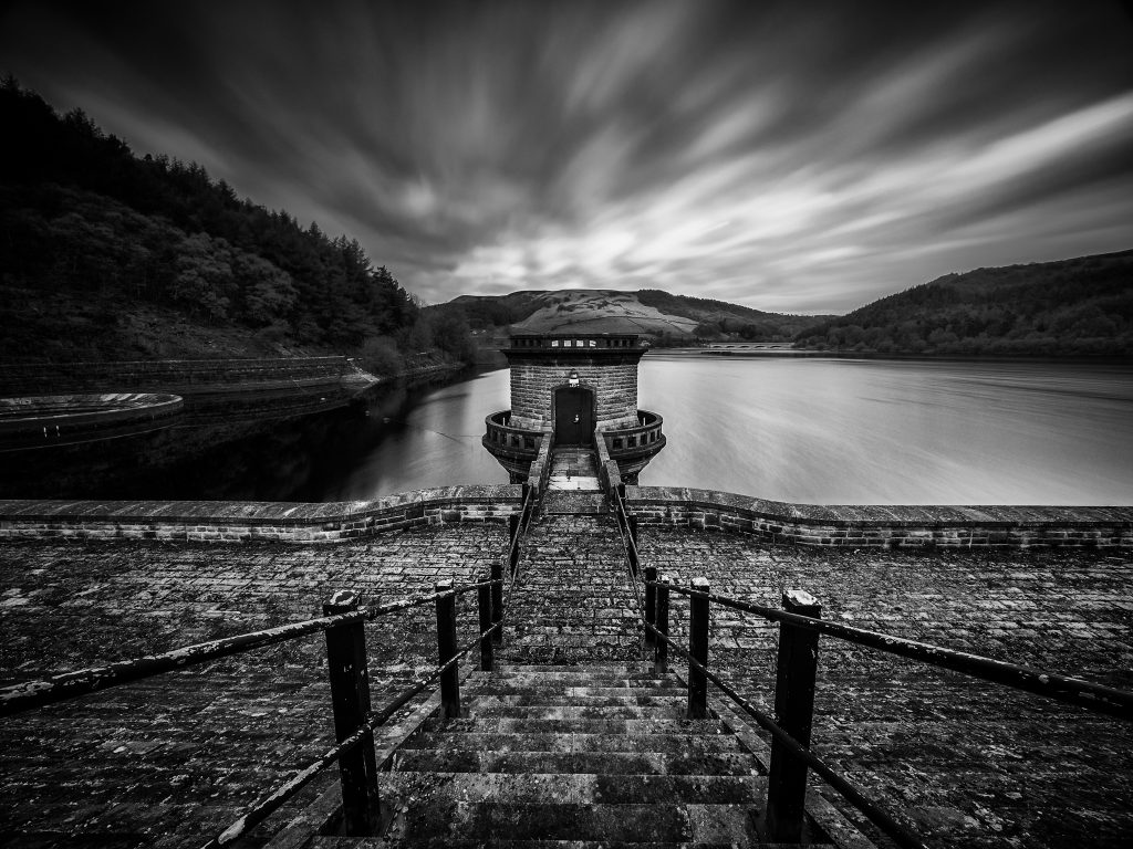 Black and white long exposure of one of the pump houses at Ladybower Reservoir in the Peak District, shot using the Benro Travel Angel tripod